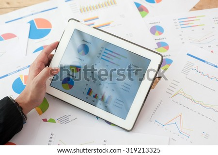 Men are opening the Tablet viewing spreadsheet excel database  graphs and statistical research has financial reports as background.