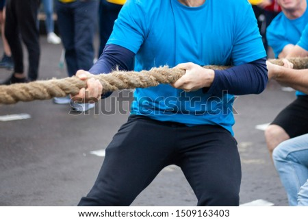 Men are pulling the rope. Sports entertainment for the strong. Strong guys pull the rope. Male power in action. Outdoor sports.