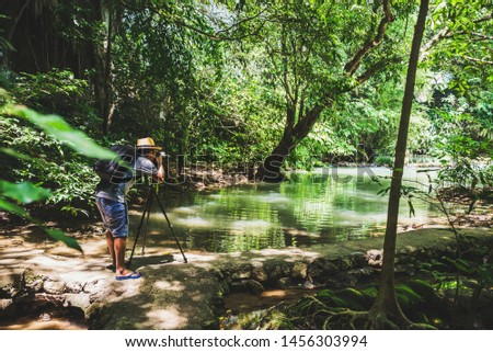 Men are trekking, taking pictures of nature on holidays. Nature Study in the forest. Hikers hiking in forest. Traveling along rain forest. A man with a backpack traveling in a tropical forest.