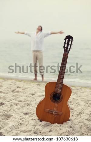 Men at the beach and guitar.