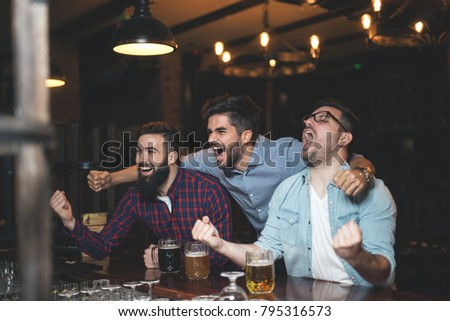 Men at the pub watcing football game and drinking beer.