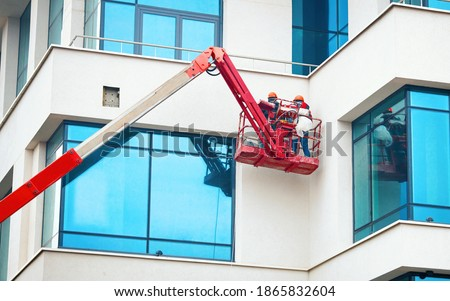 Men at work in hardhat paint facade of the building at height in lifting cradle. Finishing facade work. Construction workers at height working on crane in lifting bucket. Photo stock ©