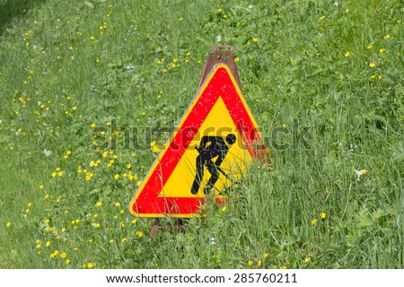 Men at work sign partially covered by a green grass field