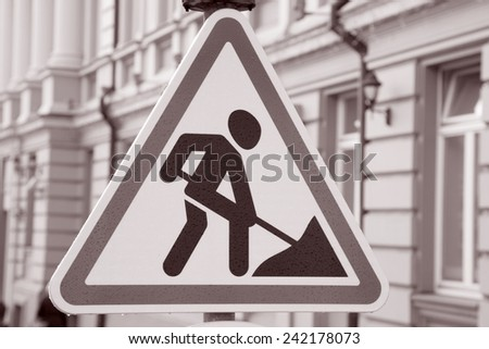 Men at Work Traffic Sign in Urban Setting in Black and White Sepia Tone