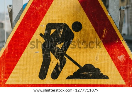 Men at works road sign, close up picture, triangle shaped red border yellow, black man