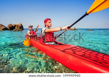 Men by sea kayaking Traveling by kayak Leisure activities on the water