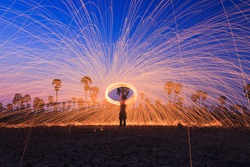 Men cast field Fire steelwool  in the sunrise time.