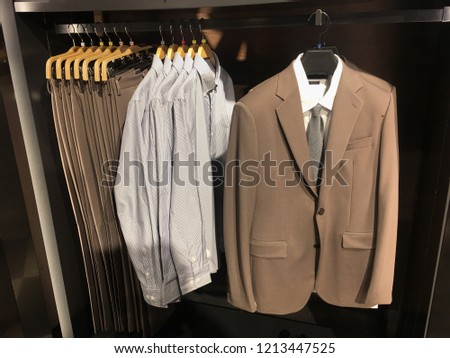 Men clothes row of clothes, suit, jacket, pants on the racks in clothing store