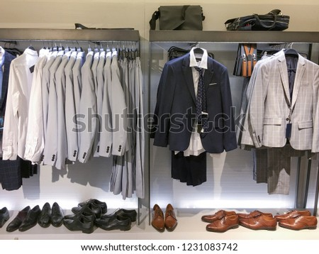 Men clothes row of clothes, suit, jacket, shoes, on the racks in clothing store