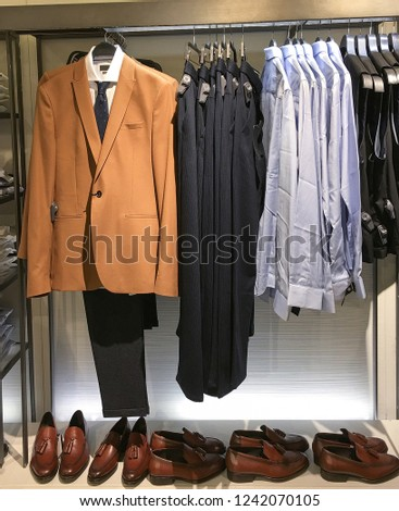 Men clothes row of clothes, suit, jacket, shoes,shirts on the racks in clothing store