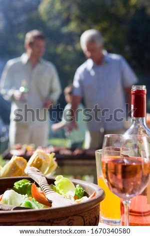 Men cooking food at family barbeque in garden with wine on table