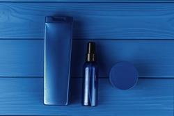 Men cosmetic bottles on classic blue background, top view