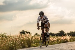 Men cycling mountain road bike at sunset.
