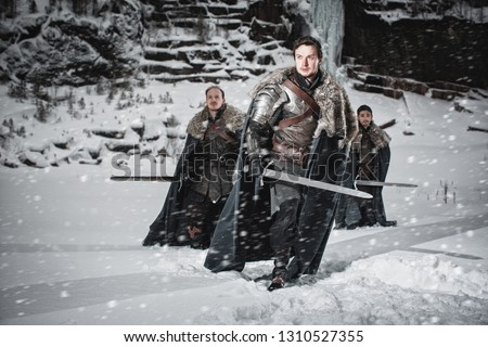 Men dressed in medieval armor and raincoats with swords in winter in the mountains under heavy snow blizzard. Fantasy group of warrior knights in winter snowy landscape