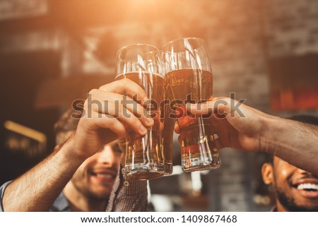 Men Drinking Draft Beer And Clinking Glasses At Pub, Closeup