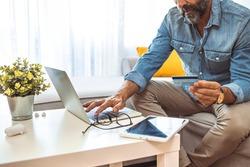 Men entering credit card information using laptop computer keyboard. Online shopping concept. Man shopping online using laptop computer and credit card