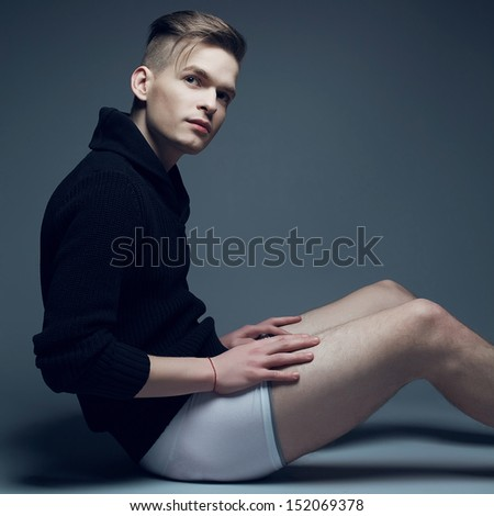 Men fashion concept. Portrait of a young fashionable man in trendy clothes and underwear sitting over gray background and holding his legs. Perfect haircut. Hipster style. Copy-space. Studio shot