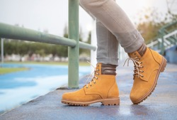 Men fashion in leather boots, Close up view on man's legs in gray jeans and yellow leather boots.