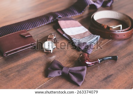 Men fashion. Men accessories. Men socks, wallet, belt, watch, tie, bow tie and smoking pipe. Still life. Business look.