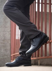 Men fashion model standing with black shoes leather.
