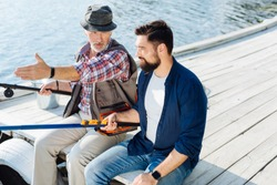 Men fishing. Bearded dark-haired man wearing smart watch fishing with his retired dad