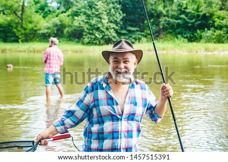 Men fishing in river during summer day. Happy fisherman fishing in river holding fishing rods. Trout on a hook. Fish on the hook #1457515391