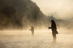 Men fishing in river with fly rod during summer morning. Beautiful fog.