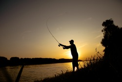 Men fishing on the river,beautiful sunset and peaceful evening, silhouette