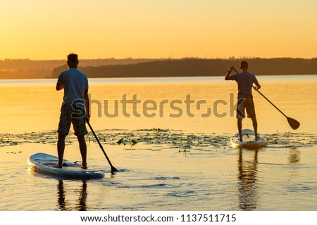 Men, friends paddling on a SUP boards in a large river during sunrise. Stand up paddle boarding - awesome active recreation in nature. Back view.