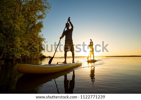 Men, friends sail on a SUP boards in a rays of rising sun. Stand up paddle boarding - awesome active recreation in nature. Backlight, wide angle.