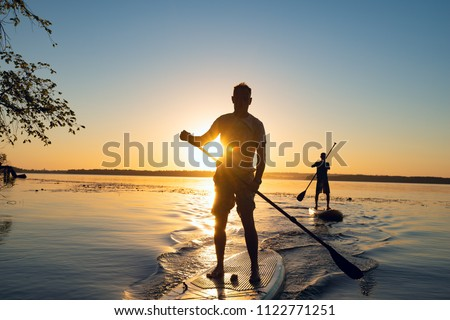 Men, friends sail on a SUP boards in a rays of rising sun. Stand up paddle boarding - awesome active recreation in nature. Backlight.