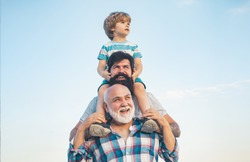 Men generation: grandfather father and grandson are hugging looking at camera and smiling. Fathers day concept. Generation concept. Weekend family play. Men in different ages