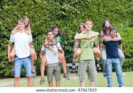 Men Giving a Piggyback Ride to  GirlFriends - stock photo