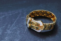 Men golden wristband bracelet decorated with luxury shinny diamonds jewelry display on the black table in the gemstone shop