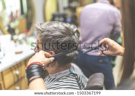 Men hairstyling and haircut in a barber shop or hair salon.