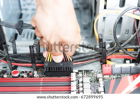 Men hand hold connect power plug and cable to power conection on motherbord in computer ATX case