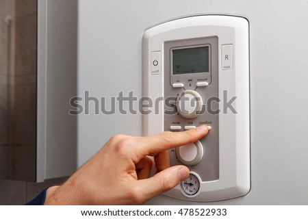Men hand setting comfort temperature button on control panel of central heating or DHW at combi boiler in restroom.
