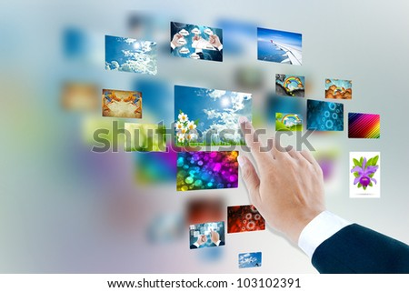 men hand using touch screen interface with pictures in frames