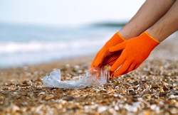 Men hand wearing protective gloves collects bottle plastic on sea beach. Problem of global plastic pollution of the Earth.