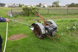 Men hand with garden hose washes an old Motor cultivator wheel with auxiliary plow with water stream on rural yard green grass background, mini tractor service, farming mechanization maintenance