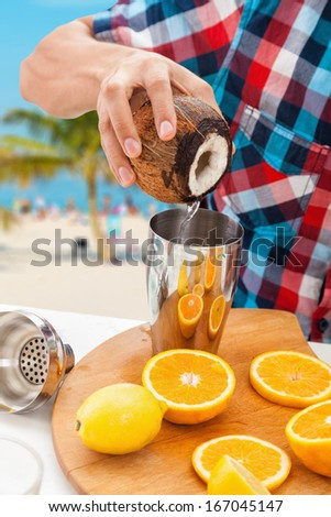 Men hands making non-alcoholic cocktail with oranges and coconut.