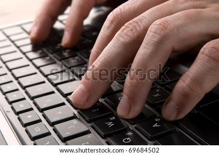 Men hands typing on a keyboard of laptop - stock photo