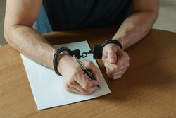 Men hands with handcuffs fill the police record, confession. on top of the police investigative detective. Arrest, bail, criminal, prison. fingerprints, criminal