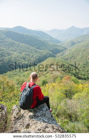 Men has a rest, sitting on the edge of the cliff
