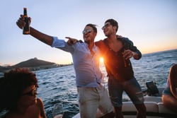 Men having a great time at boat party at sunset. Friends partying on a yacht with drinks.
