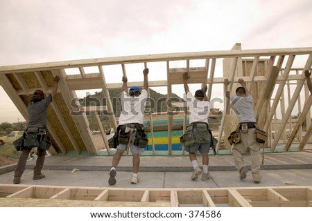 Men hoisting new wall frame