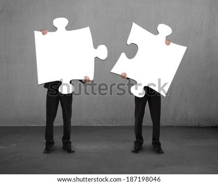 Men holding two puzzles concrete background Stock photo ©