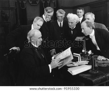 Men hovering around desk in anticipation of news