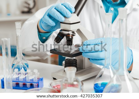 men in a laboratory microscope with microscope slide in hand