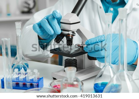 men in a laboratory microscope with microscope slide in hand.toned image.
